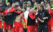 With his shirt off Liverpool's English midfielder Adam Lallana celebrates scoring their late winning goal with teammates and Liverpool's German...