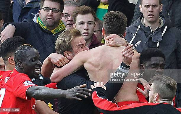 With his shirt off Liverpool's English midfielder Adam Lallana celebrates scoring their late winning goal with Liverpool's German manager Jurgen...