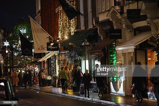 With less than one calendar month until Christmas Day consumers peruse the products on display in shop windows beneath the Christmas lights along New...