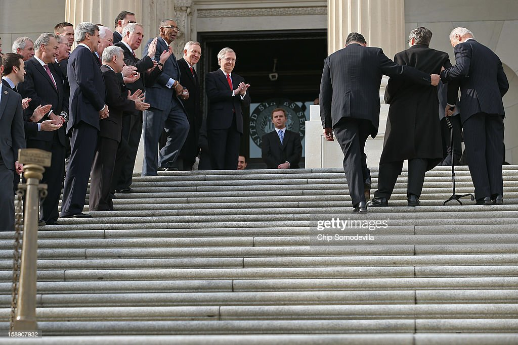 With members of the Senate and the Illinois Congressional delegation lining the steps on the east front of the Capitol, U.S. Sen. <a gi-track='captionPersonalityLinkClicked' href=/galleries/search?phrase=Mark+Kirk&family=editorial&specificpeople=2707485 ng-click='$event.stopPropagation()'>Mark Kirk</a> (R-IL) (2nd R) marks his return to the Senate by walking up the steps to the Senate door with help from U.S. Vice President Joe Biden (R) and U.S. Sen. <a gi-track='captionPersonalityLinkClicked' href=/galleries/search?phrase=Joe+Manchin&family=editorial&specificpeople=568465 ng-click='$event.stopPropagation()'>Joe Manchin</a> (D-WV) (3rd R) at the U.S. Capitol January 3, 2013 in Washington, DC. Kirk has spent the last 10 months learning to walk again after suffering a stroke on January 23, 2012.