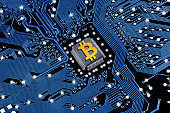 Printed circuit board with a processor and a bitcoin symbol. The concept of the mining of crypto-currency.