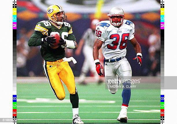 With New England Patriots safety Lawyer Milloy in pursuit Green Bay Packers wide receiver Antonio Freeman runs for a touchdown after catching a pass...