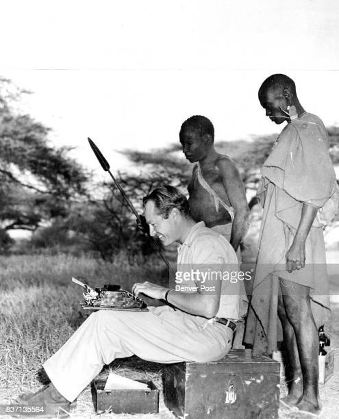 FEB 19 1950 with no coaching but plenty of curiosity two Turkana native trackers look on as Wallace Taber Denver post outdoor writer types out his...