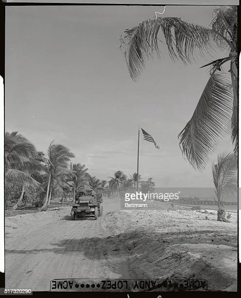With 'Old Glory' waving in the background among unsigned palm trees Seabees are shown here on Bikini atoll as they prepare for the next atom bomb test