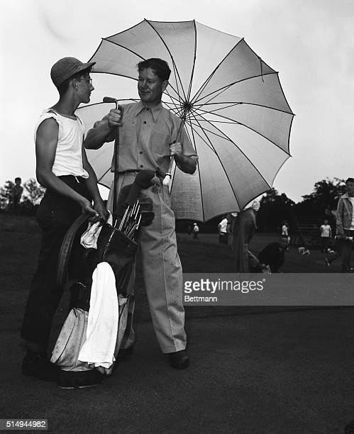 With one hand Byron Nelson takes putter from bag held by caddy Donnie Fox and with the other he holds a big umbrella to keep off the rain which...