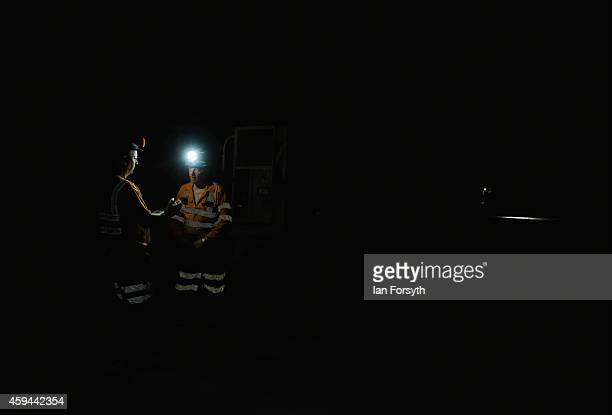 With only helmet lamps for light two miners deep underground discuss progress at the Boulby Potash mine on November 21 2014 in Boulby United Kingdom...