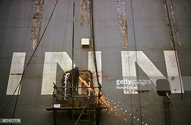 With orange sparks falling away below a shipbuilder welds while standing on a scaffolding gantry on the hull of a large German ferry at the Polish...