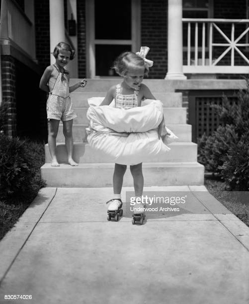 With pillows wrapped around fore and aft 4yearold Betty Buck is not taking any unnecessary chances as she tries out her first pair of roller skates...