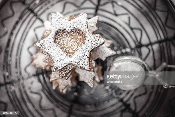 With powdered sugar sprinkled Christmas cookies and strainer lying on cake stand, close-up