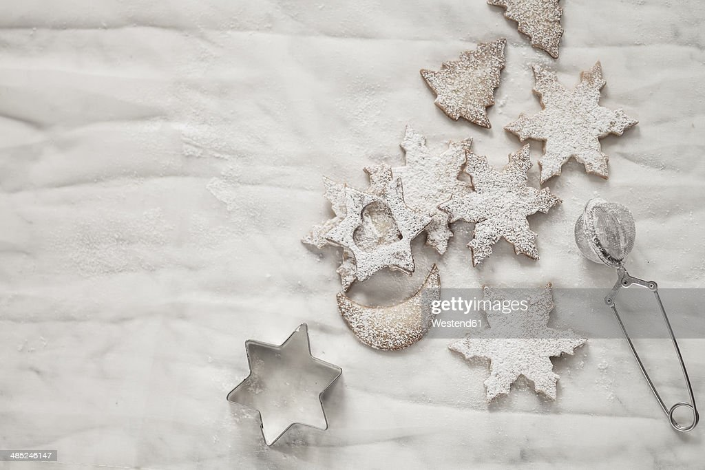 With powdered sugar sprinkled Christmas cookies, strainer and cookie cutter on white ground