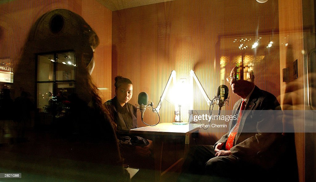 With reflections of Grand Central Station on the window of the sound booth, Justina Mejias (L) of StoryCorps assists Anaisha Rivera (C) and Art Smith (R) during their interview session December 18, 2003 at Grand Central Station in New York City. Smith, 89, who was abandoned in Gimbles dept. store in 1918 and was placed in foster care by the ChildrenÕs Aid Society and Rivera, who is also a foster child, interviewed him in an interview arranged by the aid society. StoryCorps is an oral history project that enables people to interview imortant people in their lives and receive a CD recording. The interview is then placed in the collection of the American Folklife Center at the Library of Congress.
