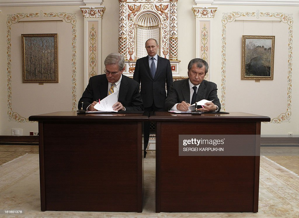 With Russia's President Vladimir Putin (back) watching Russian oil giant Rosneft CEO Igor Sechin (R) and President of ExxonMobil Exploration Company Stephen Greenlee sign documents at the Novo-Ogaryovo state residence outside Moscow, February 13, 2013. Rosneft signed yesterday an agreement with ExxonMobil giving the US super-major access to seven Arctic fields in exchange for the Russian firm's possible participation in a lucrative Alaskan gas project.