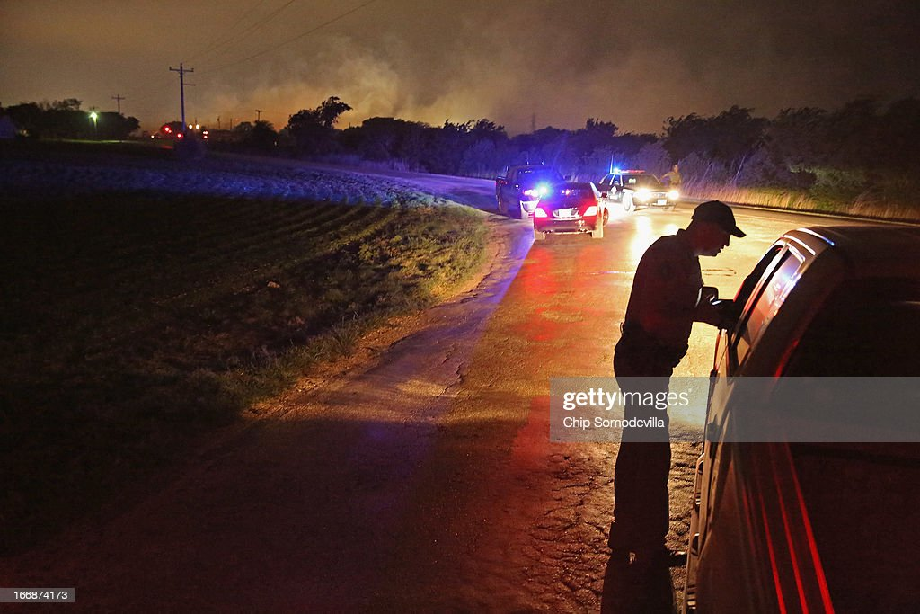 With smoke rising in the distance, a law enformcement officer runs a check point at the perimeter about half a mile from the West Fertilizer Company April 18, 2013 in West, Texas. A massive explosion at the fertilizer company injured more than 100 people and left damaged buildings for blocks in every direction. The death toll from the blast, which occured as firefighters were tackling a blaze, is as yet unknown.