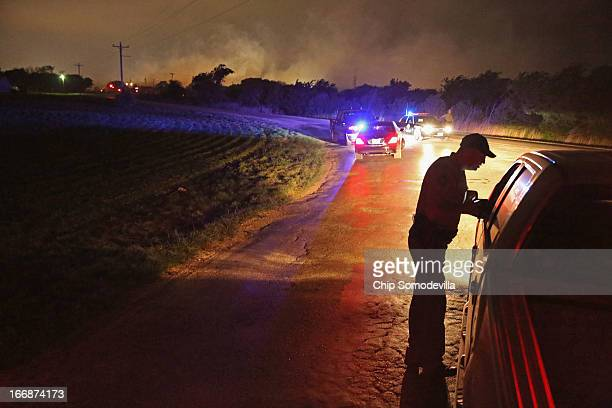 With smoke rising in the distance a law enformcement officer runs a check point at the perimeter about half a mile from the West Fertilizer Company...