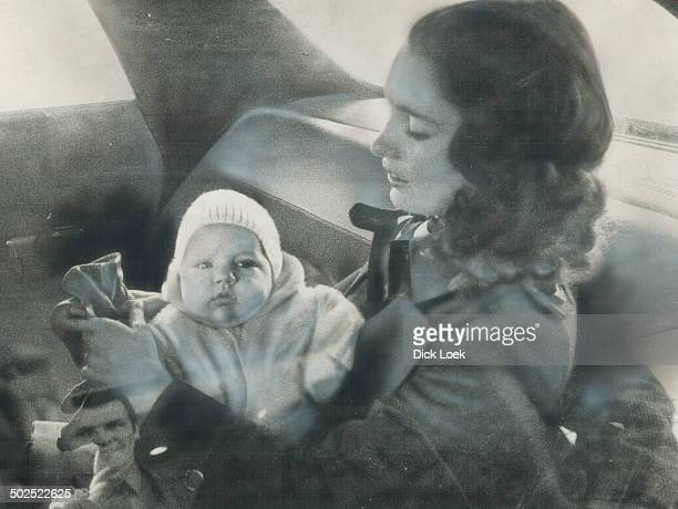 With son Justin in her lap Margaret Trudeau wife of Prime Minister Pierre Trudeau sits in a car outside the Inn on the Park just before a lunchtime...