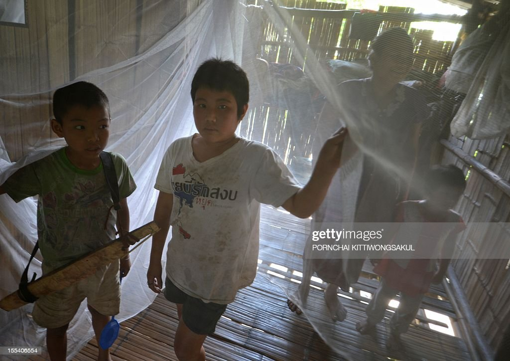 with story HEALTH-MALARIA-THAILAND-MYANMAR BY Dan Rook Children stand inside a mosquito net at Sai Yoke district in Kanchanaburi province near the Thai-Myanmar border on October 26, 2012. For more than a decade, the fast-acting treatment artemisinin has been Thailand's most potent weapon in the long-running battle against malaria, contributing to a sharp drop in the number of deaths. AFP PHOTO / PORNCHAI KITTIWONGSAKUL