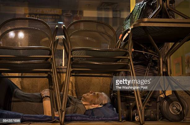 With suitcases in arms reach homeless woman Wanda Witter beds down in her sleeping spot outside the Au Bon Pain on 13th and G Street in Washington DC...