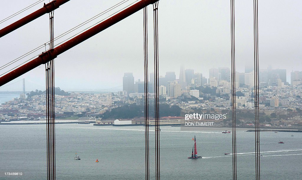 With supports of the Golden Gate Bridge in the foreground Emirates Team New Zealand sails their AC-72 Racing Yacht in San Francisco Harbor during the America's Cup in San Francisco, California on July, 14, 2013. AFP PHOTO/Don Emmert
