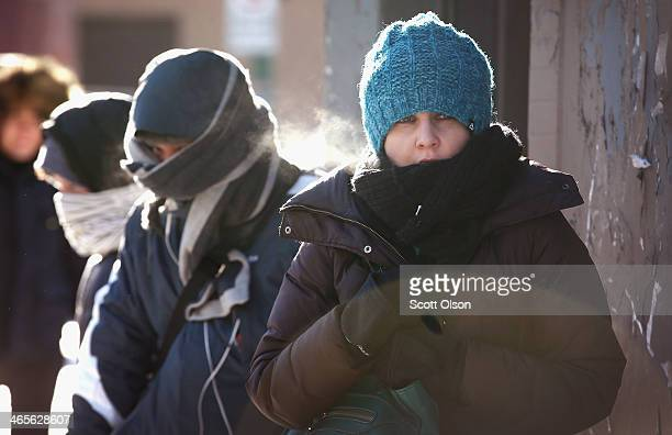 With temperatures hovering around 10 degrees commuters wait for a bus January 28 2014 in Chicago Illinois The city has had 18 days at or below zero...