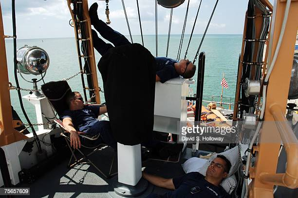 With the boat's air conditioner broken crew members Nick McDole left Dan Finke and David Singleton all try to catch up on sleep on the open bridge of...