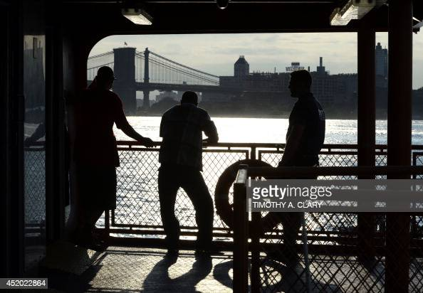 With the Brooklyn Bridge in the background commuters on the Staten Island Ferry watch the morning sunrise in the New York Harbor in lower Manhattan...