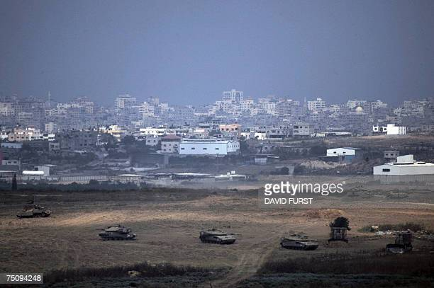 With the Gaza Strip skyline in the distance Israeli tanks and armored personnel carriers maneuver inside the northern Gaza Strip 06 July 2007 Israeli...