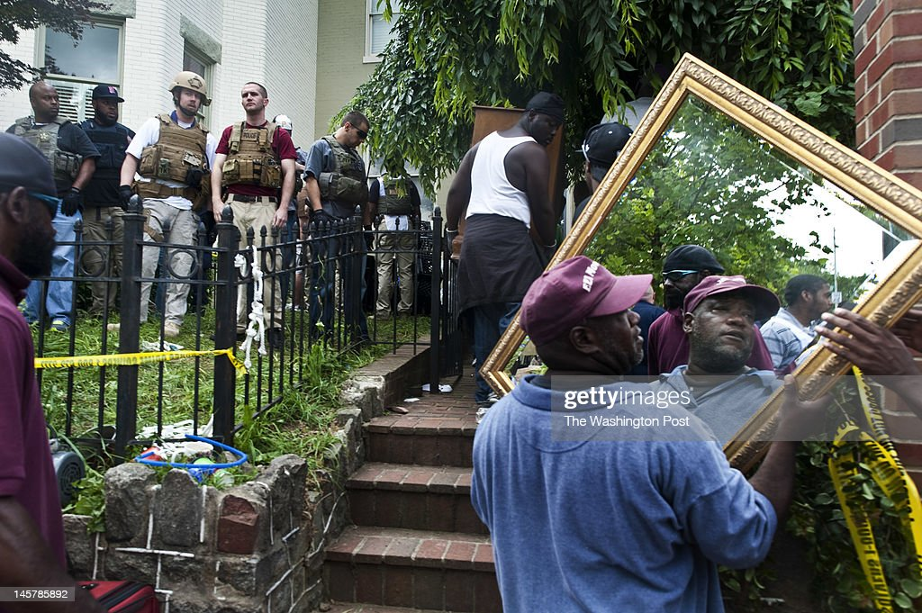 With the help of hired movers, US Marshalls remove the personal belongings from 4 apartments as they evict residents from 917 Maryland Avenue NE, while Occupy Home protestor behind police tape watch, Tuesday, June 5, 2012.