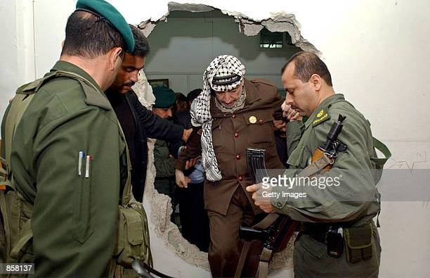 With the help of his bodyguards Palestinian leader Yasser Arafat climbs March 16 2002 through a hole in the wall made by Israeli troops during their...