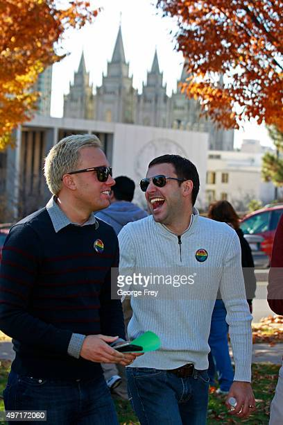 With the historic Mormon Salt Lake Temple in the background Chris Wade and Sam Wade laugh as they wait in line to submit their resignations from the...