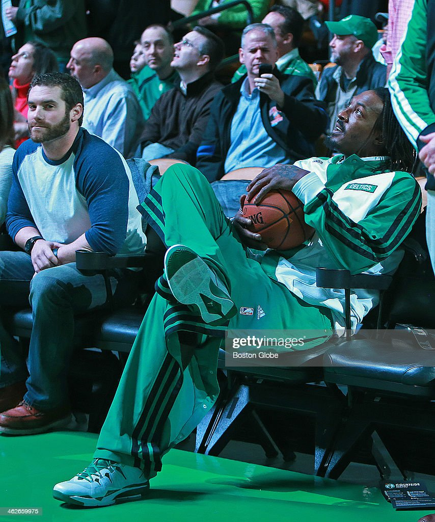 With the house lights down as the starting lineups are introduced, Celtics reserve forward Gerald Wallace took a front row court-side seat to watch. The Boston Celtics hosted the Houston Rockets in a regular season NBA game at TD Garden.