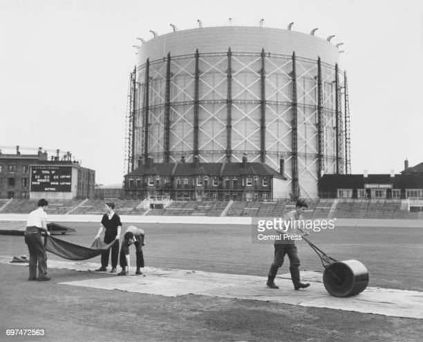 With the landmark gasometer forming the backdrop groundsmen work to roll and cover the wicket in preparation for the Surrey County Cricket Club v The...