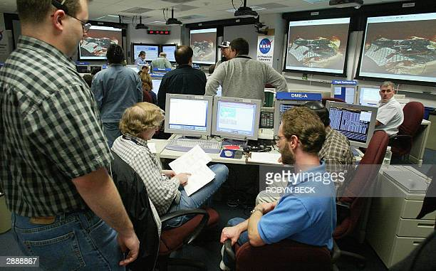 With the latest photos from Mars projected on the wall engineers work in the Mars Exploration Rover control room at NASA's Jet Propulsion Laboratory...
