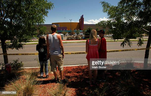 With the mall reopened people walk up to the police tape still encircling the parking lot at the Century 16 Theaters July 22 2012 in Aurora Colorado...