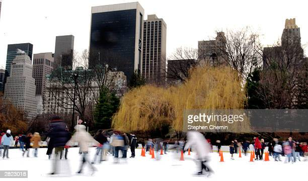 With the New York City skyline in the background skaters enjoy the Wollman ice rink December 19 2003 in New York's Central Park