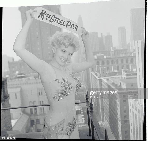 With the New York city skyline offering an impressive backdrop pretty Christina Logan displays her title above her head as she poses atop the Beverly...