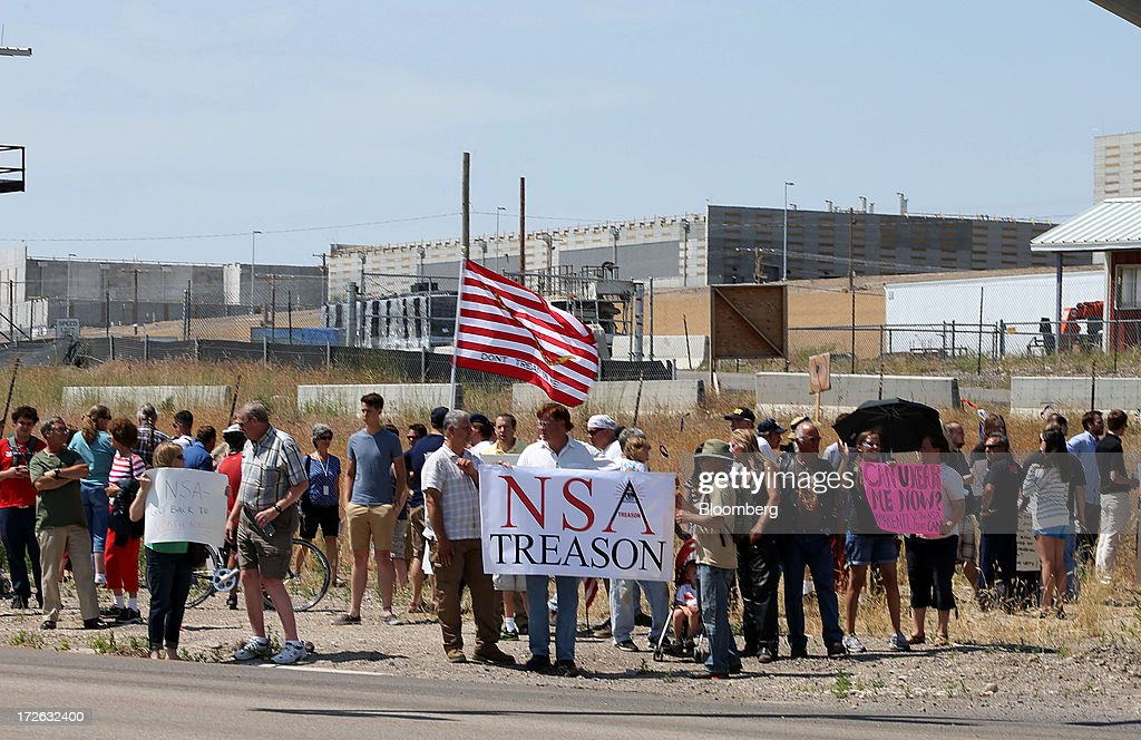 With the NSA Data Center in the background, protesters chant and sing songs at the entrance of the new National Security Agency data center facility being built in Bluffdale, Utah, U.S., on Thursday, July 4, 2013. President Vladimir Putin said NSA whistleblower Edward Snowden must quit hurting American interests if he wants to remain in Russia, after an official said the fugitive applied for asylum here. Photographer: George Frey/Bloomberg via Getty Images