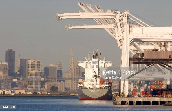 With the San Francisco skyline in the background a loaded cargo ship sits idle at the American Presidents Line terminal at the Port of Oakland...