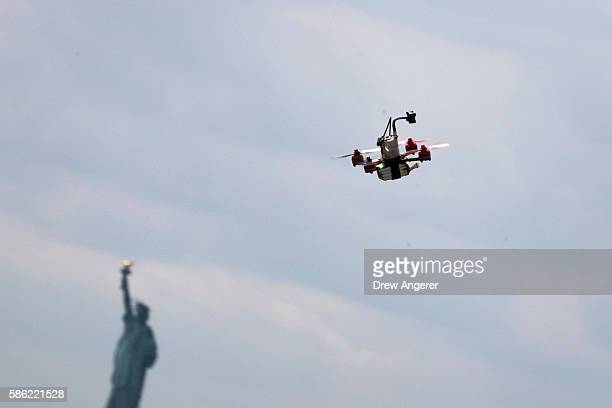 With the Statue of Liberty behind it a drone flies in the sky during practice day at the National Drone Racing Championships on Governors Island...