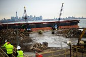 With the Statue of Liberty in the background cranes and heavy machinery maneuver piles of shredded metal material at Sims Metals Management the...