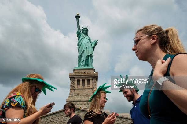 With the Statue of Liberty in the background visitors walk around Liberty Island August 8 2017 in New York City Immigration continues to be a hotly...