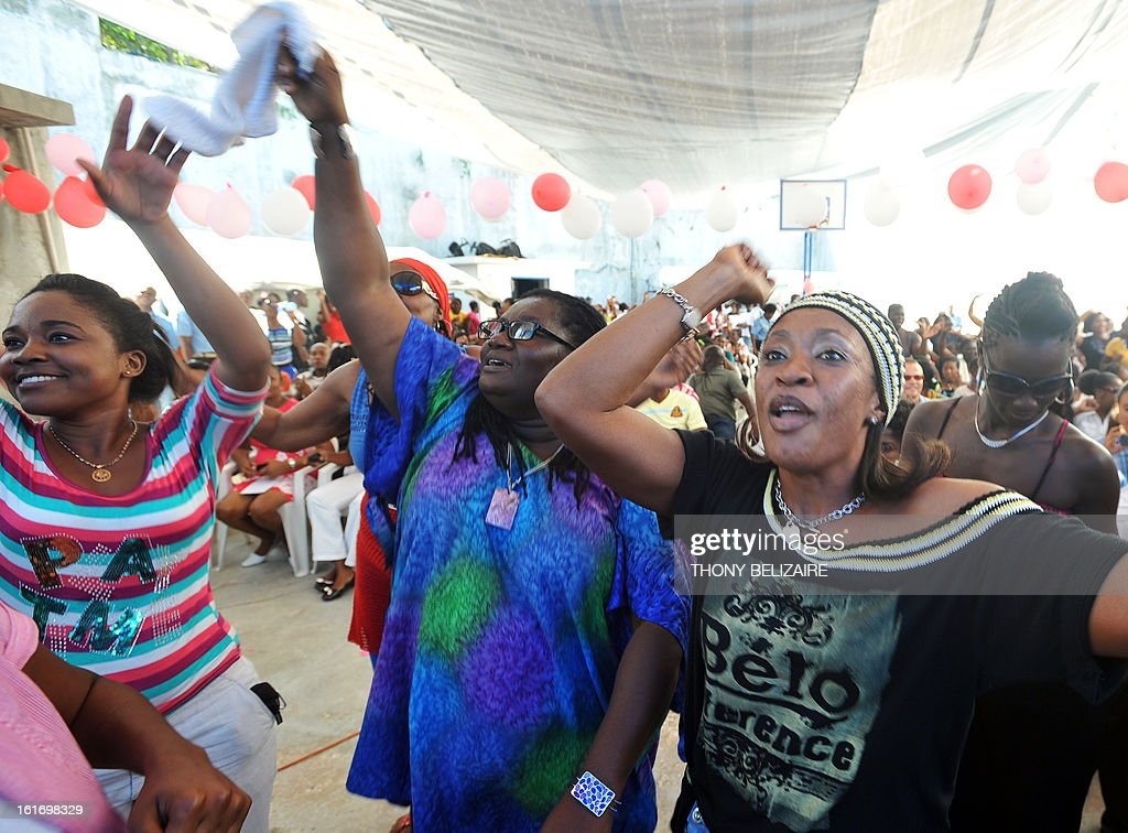 With the support of the International Red Cross, people dance to Haitian singer Jean Belony Murat as he plays on February 14, 2013 a music concert on Valentine's Day for Haitian prisoners in the civil prison of Petion-ville , a suburb of Port-au-Prince. AFP PHOTO/ Thony BELIZAIRE