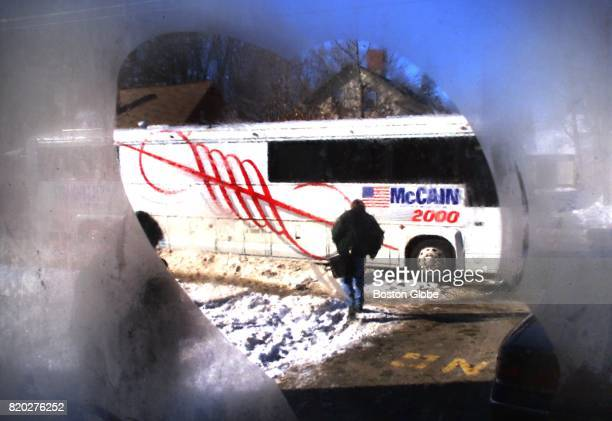 With the temperature 12 degrees outside the McCain campaign bus sits outside Exeter High School seen through a fogged window while presidential...