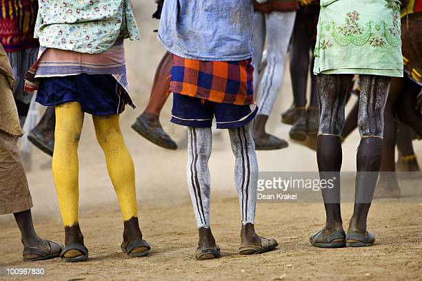 With their legs painted in ceremonial decorations members of the bride's family watch as a dance takes place during a wedding celebration in the...
