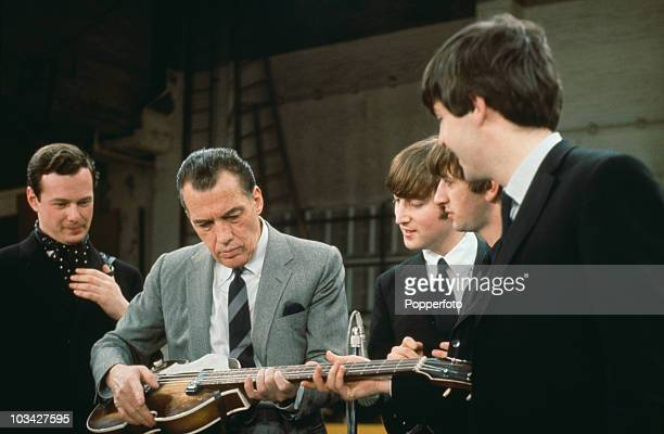 Members of the Beatles and their manager Brian Epstein look on as American TV host Ed Sullivan tries out Paul's Hofner violin bass during rehearsals...