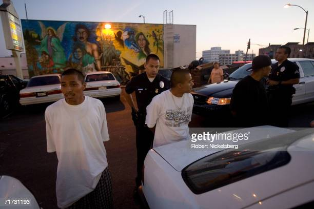 With three 18th Street gang members detained a Los Angeles gang police officer handcuffs a member on August 4 2006 in the Rampart area in Los Angeles...