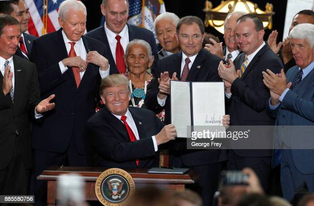 With Utah officials surrounding him US President Donald Trump shows an executive order he signed reducing the Grand StaircaseEscalante National...