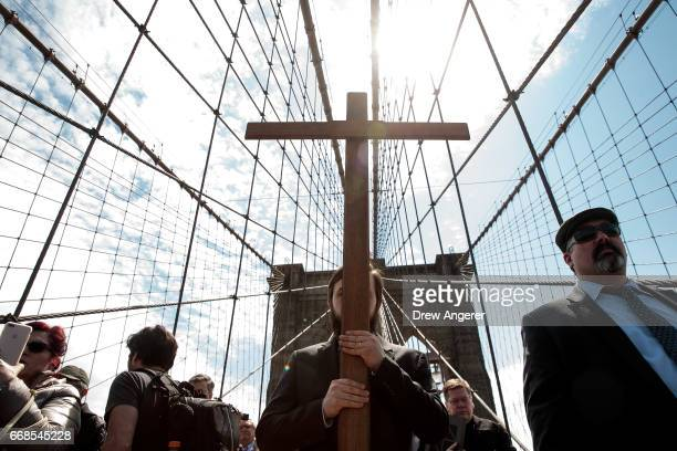 With Vitality Kuzmin carrying the cross the Way of the Cross procession makes its way across the Brooklyn Bridge on Good Friday April 14 2017 in New...