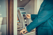 Businessman inserting credit card and withdrawing money form ATM machine.