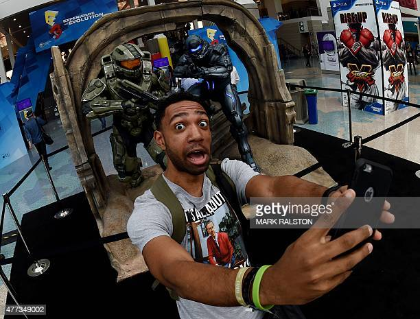 JD Witherspoon takes a 'selfie' in front of action figures from the 'Halo' game on the opening day of the Electronic Entertainment Expo known as E3...