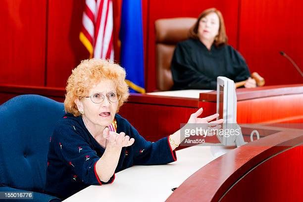 Witness testifying at the stand in federal court, judge watching